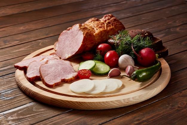 Prosciutto guarnito con verdure, frutta ed erbe aromatiche con salse e pane su un piatto di legno su un tavolo di legno scuro.