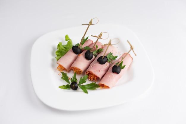 Involtini di prosciutto decorati con olive su spiedini su fondo bianco