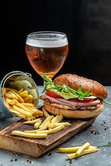 Sandwich al prosciutto. hamburger con prosciutto, pomodoro e lattuga. birra e patatine fritte, hamburger con patatine fritte e salse. immagine verticale. posto per il testo,