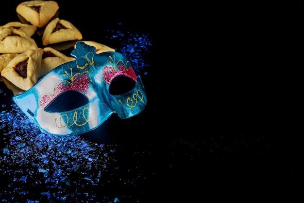 Biscotti hamantaschen con maschera blu su sfondo nero. holiday purim.