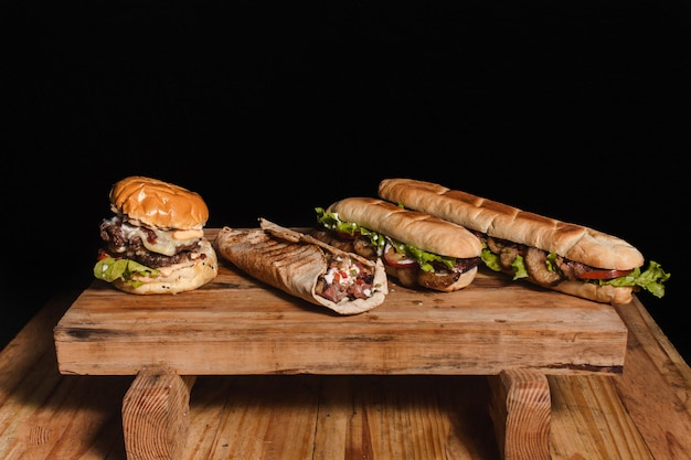 Un hamburger, un filetto arabo e due panini con bistecca su un tavolo di legno rialzato con uno sfondo nero.
