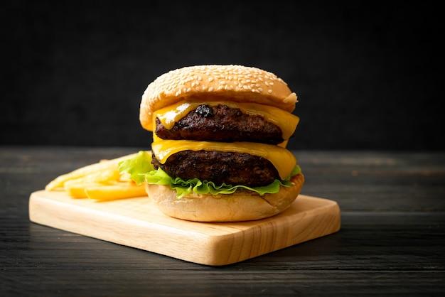 Hamburger o hamburger di manzo con formaggio e patatine fritte - stile di cibo malsano