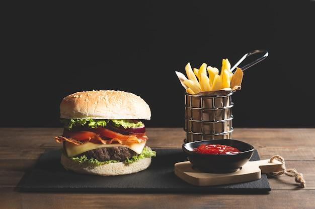 Hamburger chips e ketchup su base in legno su fondo nero.