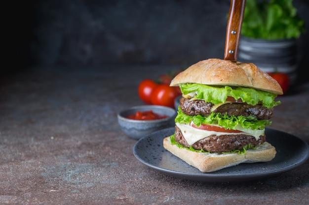 Hamburger con hamburger di carne di manzo e verdure fresche su sfondo scuro. gustoso fast food.