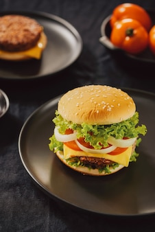 Hamburger con hamburger di carne di manzo e verdure fresche su sfondo scuro. gustoso fast food