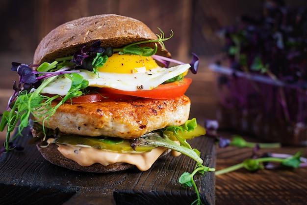 Hamburger con hamburger di pollo, pomodori, cetrioli sottaceto e uovo fritto