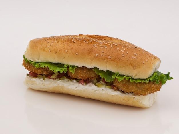 Hamburger con cotoletta e sottaceti su sfondo bianco con riflesso