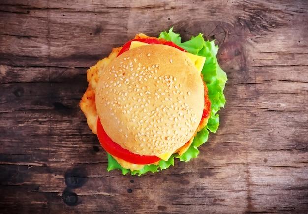 Hamburger con pomodoro fresco, insalata, formaggio e carne su un vecchio tavolo di legno.