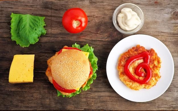 Hamburger con verdure fresche, formaggio e carne su un vecchio tavolo di legno. ingredienti dell'hamburger