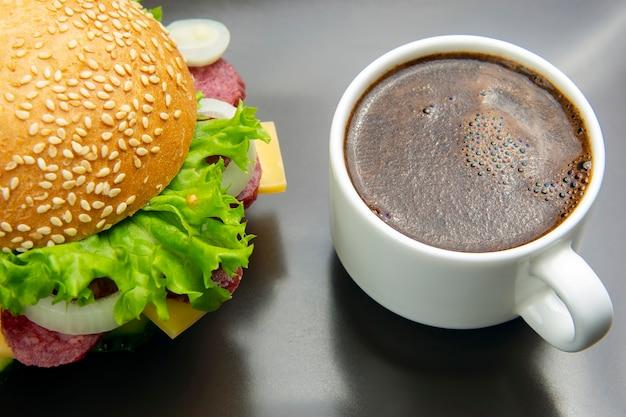 Hamburger con verdure e salsiccia e caffè. fast food e colazione. calorie e dieta.