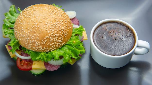 Hamburger con verdure e salsiccia e caffè su uno sfondo grigio. fast food e colazione. calorie e dieta.