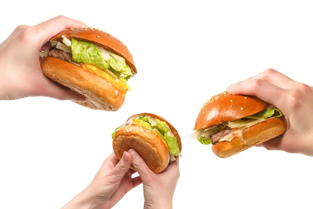 Hamburger in mani di donna isolate su una superficie bianca. vista dall'alto.