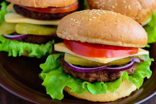 Hamburger a casa (panino, pomodoro, cetriolo, anelli di cipolla, lattuga, braciole di maiale, formaggio) in una ciotola di argilla su uno sfondo di legno. avvicinamento