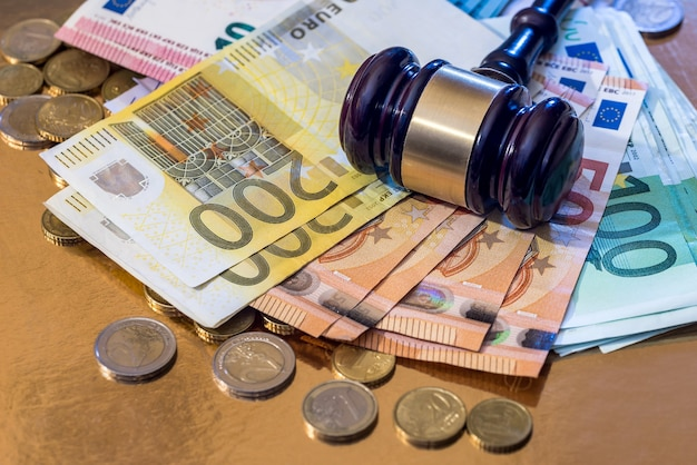 Martello con molte banconote e monete in euro