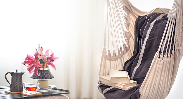 Una sedia pensile in stile boho con libri, teiera e tazza di tè. il concetto di riposo e comfort domestico.