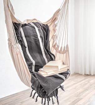 Sedia amaca in stile boho con una pila di libri. concetto di luogo accogliente per rilassarsi a casa.