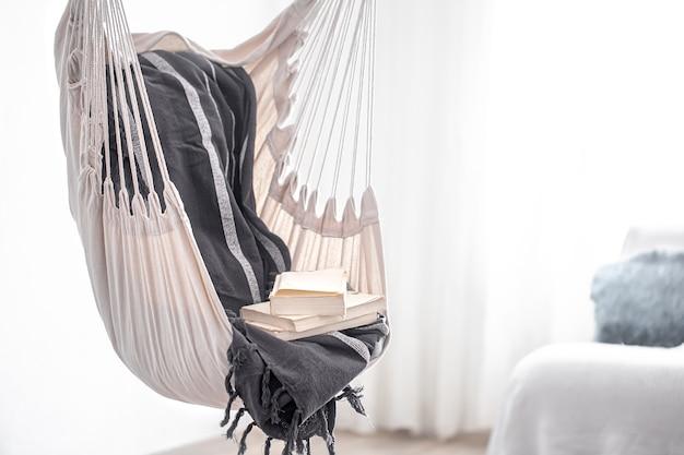 Una sedia pensile in stile boho con una pila di libri. il concetto di luogo accogliente per rilassarsi a casa.