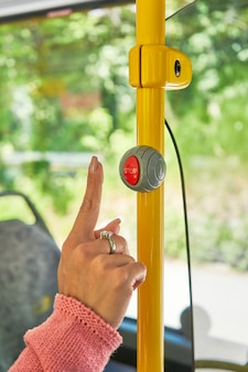 Mano che sta per premere il pulsante di arresto dell'autobus da vicino