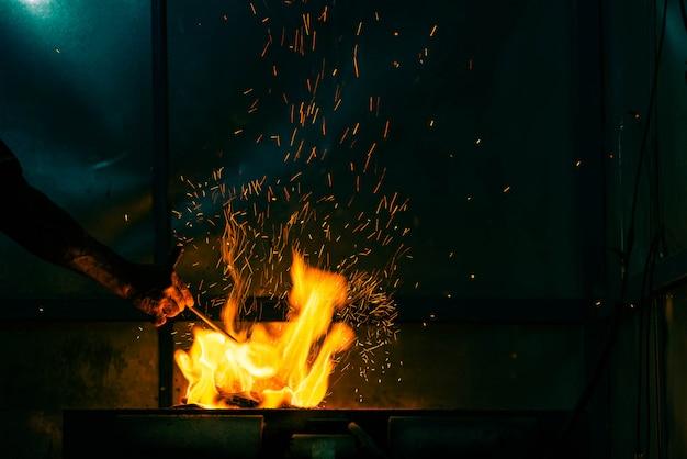 La mano regola il carbone ardente per la cottura con la fiamma e la scintilla del fuoco su fondo scuro
