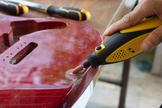Mano di artigiano adulto che fissa la vecchia chitarra classica aggiungendo cavo e accordando lo strumento. primo piano di mani e tavolozza