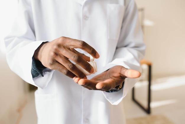 Mano del medico afroamericano che tiene le pillole sopra priorità bassa bianca dello studio, ritagliata