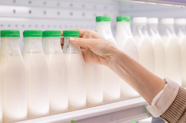 Mano del consumatore femminile invecchiato che prende la bottiglia di plastica della bevanda lattiera acida fresca mentre sceglie i prodotti alimentari nel supermercato
