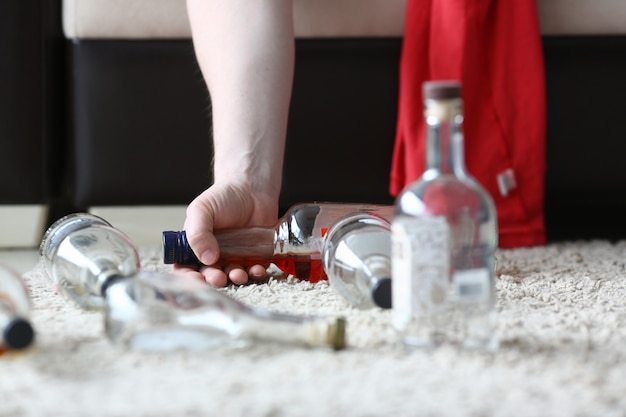 La mano di un alcolizzato tiene la metà