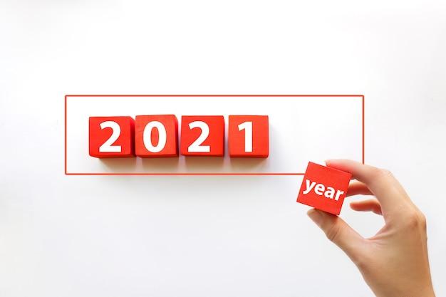 Disposizione a mano di blocchi rossi impilati in linea con il testo 2021 anno. concetto di business per il successo della crescita