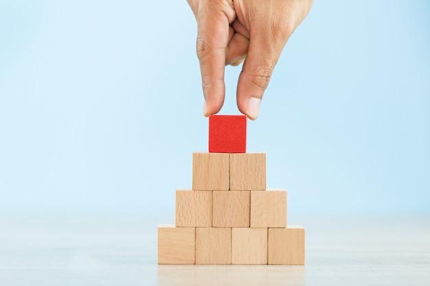 Mano che organizza l'impilamento del blocco di legno rosso come scala a gradino, con il concetto di una fiorente attività in corso per il successo.