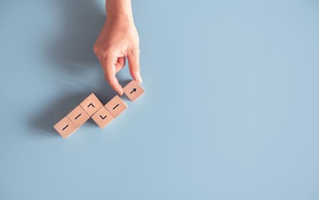 Mano che organizza l'impilamento del blocco di legno come successo di crescita.