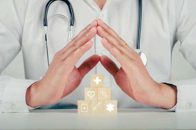 Sistemare a mano l'impilamento del blocco di legno con l'icona medica sanitaria. assicurazione sanitaria - concetto di salute