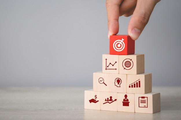 Passi la disposizione del blocco di legno che impila con la freccia e l'affare dell'icona, miranti al concetto di affari.