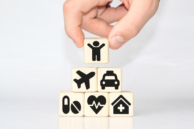Mano che organizza l'impilamento del blocco di legno con l'icona sanitaria medica, assicurazione per il tuo concetto di salute