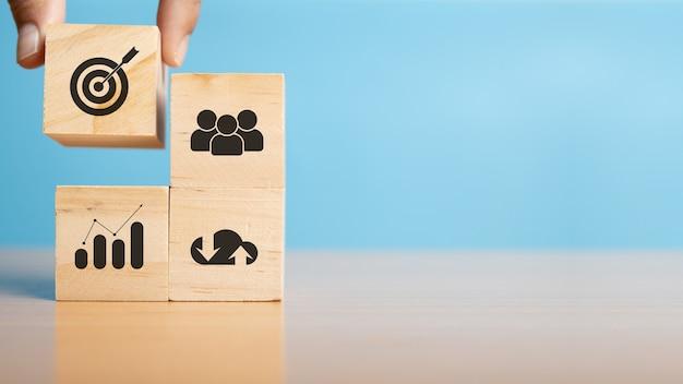 Sistemazione a mano blocco di legno con strategia aziendale icona e piano d'azione. obiettivo e obiettivo, successo e concetto di obiettivo aziendale, gestione del progetto, sviluppo della strategia aziendale. copia spazio.