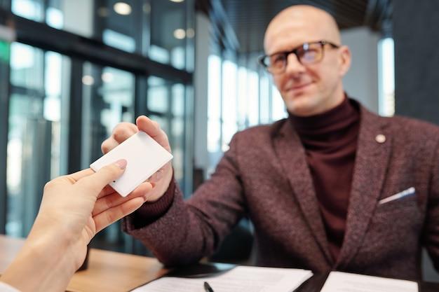 Mano dell'uomo d'affari maturo calvo in occhiali da vista e formalwear prendendo carta da camera d'albergo vuota al banco della reception
