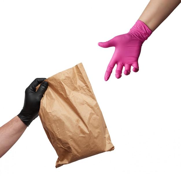 La mano in un guanto di lattice nero contiene un pacchetto marrone pieno e una mano femminile in un guanto rosa raggiunge un oggetto