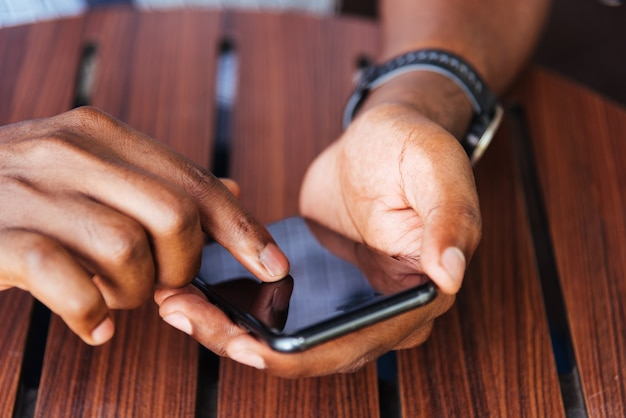 Persona dell'uomo di colore della mano che tiene un telefono astuto moderno e che tocca un dito alla schermata vuota