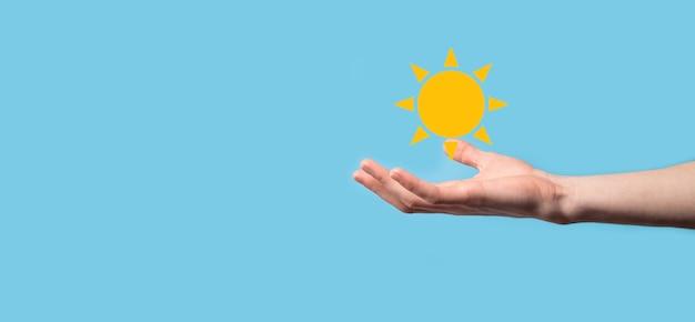 La mano su sfondo blu tiene il simbolo dell'icona del sole. fonte di elettricità sostenibile, concetto di alimentazione. approccio tecnologico eco-compatibile.