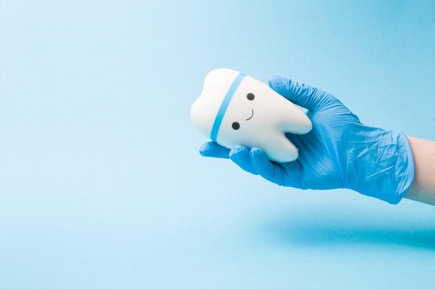 La mano in un guanto medico di gomma usa e getta blu tiene un dente sorridente del giocattolo su una superficie blu