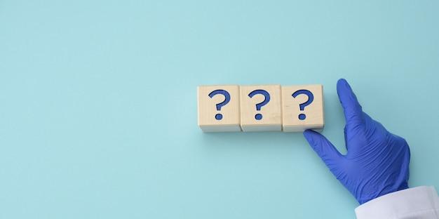 Una mano in un guanto medico blu tiene cubi con punti interrogativi su una superficie blu. il concetto di domande sconosciute, indovinello, senza risposta, copia dello spazio