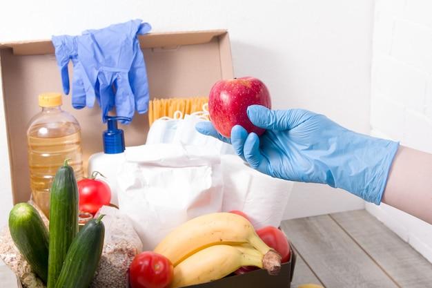 La mano in un guanto usa e getta di gomma blu mette una mela rossa nella scatola delle donazioni