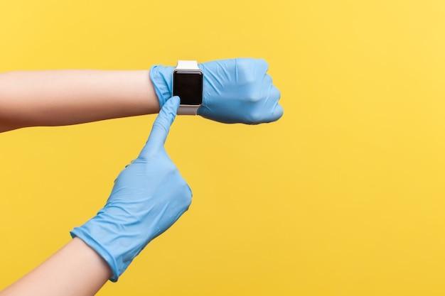Mano in guanti chirurgici blu che tengono e mostrano l'orologio intelligente da polso e puntano allo schermo vuoto.