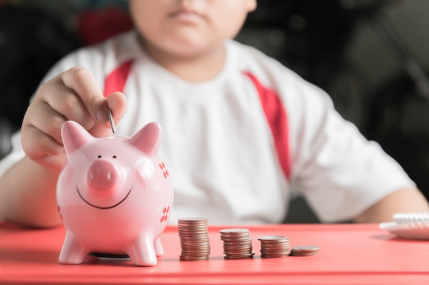 Mano ragazzo mise moneta per salvadanaio, risparmiando denaro per l'istruzione