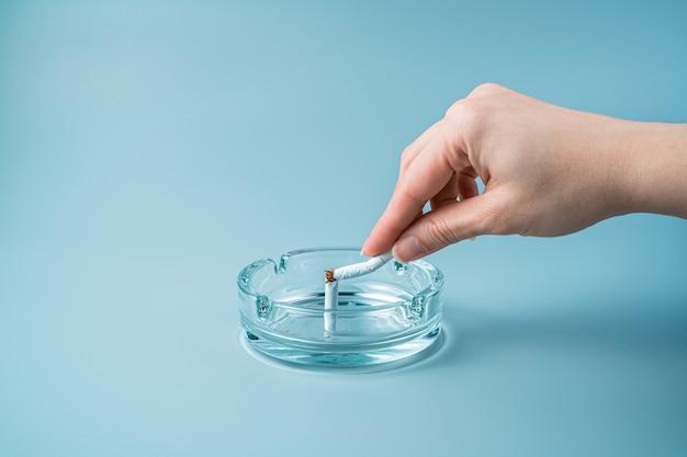 Una mano rompe una sigaretta in un portacenere su sfondo blu.