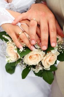 Mano della sposa e mano dello sposo con anelli su un bouquet da sposa contro un vestito bianco