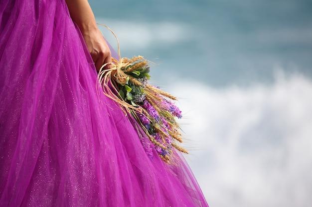 Mano della sposa con un bouquet da sposa