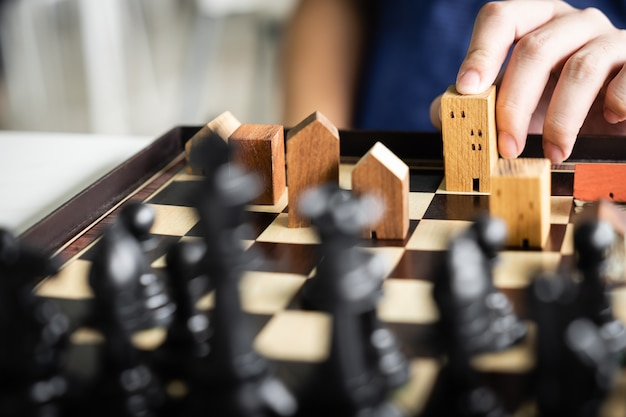 Mano dell'uomo d'affari in movimento edificio e modelli di casa nel gioco degli scacchi