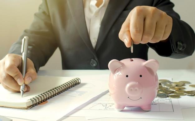 Mano di una donna d'affari che tiene una moneta di denaro su un salvadanaio, concetto di risparmio di denaro e un futuro permanente.