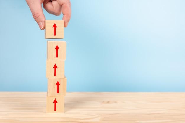 Mano dell'uomo d'affari che organizza i blocchi di legno che impilano con la freccia rossa sul tavolo, sfondo blu
