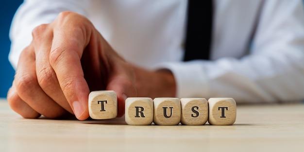 La mano di un uomo d'affari che monta la fiducia di parola ha scritto sui dadi di legno.